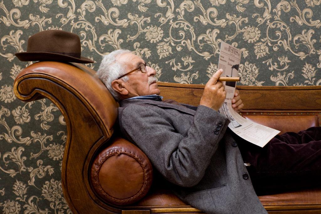 Senior liest in der Zeitung, während er gemütlich auf dem Sofa liegt.