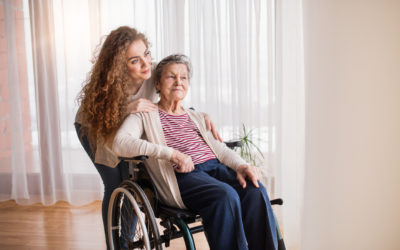 A teenage girl with grandmother in wheelchair at home. Family and generations concept.